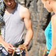 Rock climbing man showing woman rope knot — Stockfoto