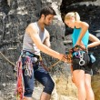 Rock climbing man showing woman rope knot — Foto de Stock