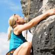 Rock climbing blond woman on rope sunny - Stock Photo