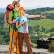 Hiking young couple point at panoramic view — Stock fotografie