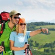 Hiking young couple point at panoramic view - Stok fotoğraf