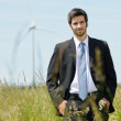 Green energy - Young businessman in field windmill — Stock Photo #6139038