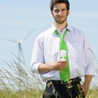 Green energy businessman in field hold bulb — Stock Photo #6139045