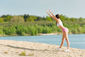 Summer sport active woman stretching on beach — Stock Photo