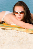 Young sexy bikini model relaxing with sunglasses — Stock Photo