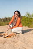 Camping happy woman making campfire on beach — Stock Photo