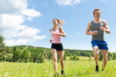 Sportive young couple jogging meadows sunny summer — Stock fotografie