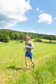 Sportive young man jogging meadows sunny summer — Foto Stock