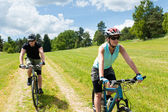 Sport happy couple riding bicycles in coutryside — Stock Photo