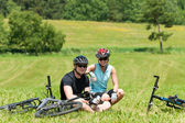 Sport mountain biking couple relax sunny meadows — Stock Photo