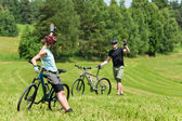 Sport mountain biking couple greeting in meadows — Stock Photo