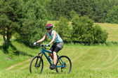 Sport mountain girl biking uphill sunny meadows — Zdjęcie stockowe