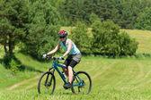 Sport mountain girl biking uphill sunny meadows — Stock Photo