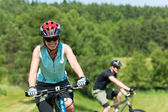 Sport mountain couple biking uphill sunny meadows — Zdjęcie stockowe