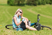 Sport mountain biking girl relax in meadows — Stock Photo