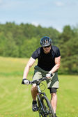 Sportive man mountain biking uphill sunny meadows — Foto Stock