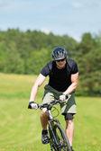 Sportive man mountain biking uphill sunny meadows — Stock Photo