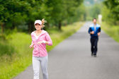 Jogging sportive young couple running park road — Стоковое фото