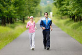 Jogging sportive young couple running park road — Foto Stock