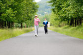 Jogging sportive young couple running park road — ストック写真