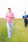 Jogging sportive young couple running meadow field — Stok fotoğraf