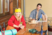 Tramping młoda para zrelaksować się przy drewnianym stołem — Zdjęcie stockowe