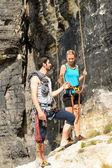 Rock climbing young man showing woman rope — Stock Photo