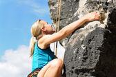 Rock climbing blond woman on rope sunny — Stock Photo