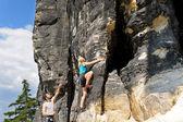 Mujer de rubio male instructor escalada roca soleada — Foto de Stock