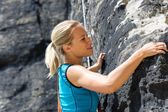 Rock climbing blond woman on rope — Stock Photo
