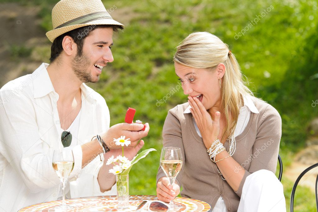 Young man proposing to girlfriend offering engagement ring sunny terrace — Stock Photo #6138807