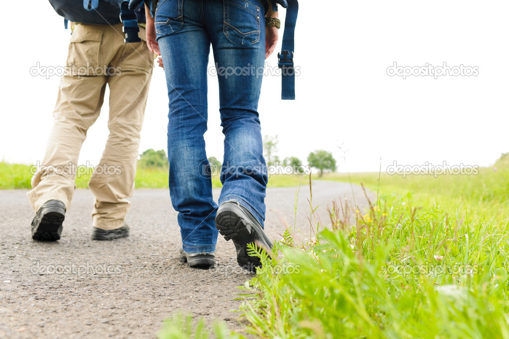 Close-up of hiking couple legs backpack on asphalt road — Stock Photo #6138885