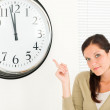 Punctual businesswoman attractive point at clock — Stock Photo