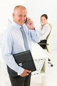 Zralé podnikatel volání drží aktovku — Stock fotografie