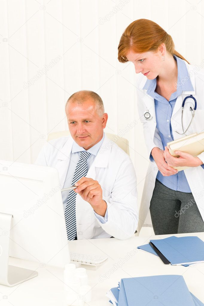 Medical senior doctor male with professional  female colleague point computer — Stockfoto #6287830