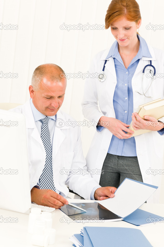 Medical doctor team senior man with female colleague look x-ray — Stock Photo #6287837
