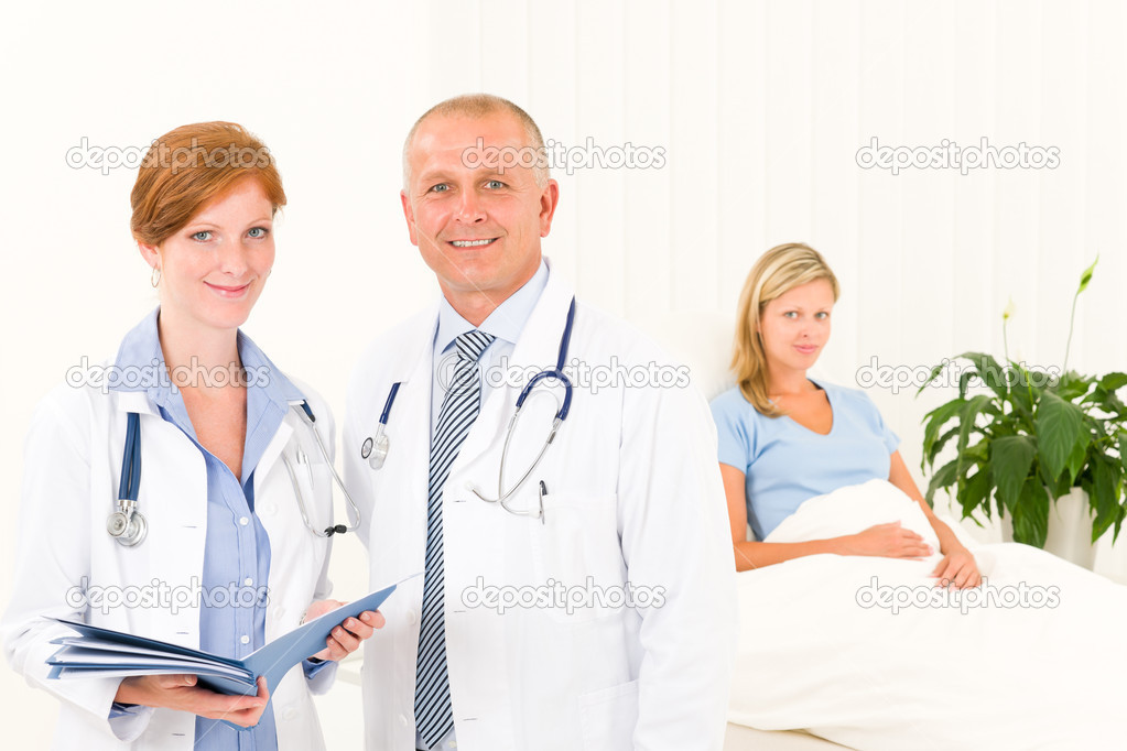 Two medical doctors professional with hospital patient lying in bed — Lizenzfreies Foto #6287908