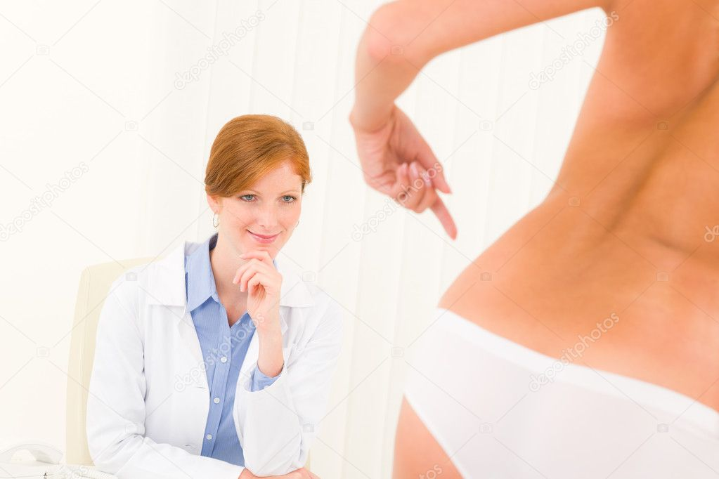 Plastic surgery consultation female doctor patient point skin on hips — Stock Photo #6288008