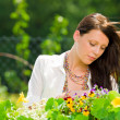 Summer garden beautiful woman care color flowers — Stock Photo