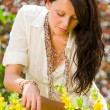 Beautiful woman sunny garden care yellow flowers — Stock Photo #6441144