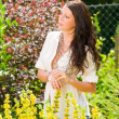Garden beautiful young woman sunny yellow flowers — Stock Photo #6441155