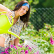 Stock Photo: Gardening smiling woman watering can violet flower