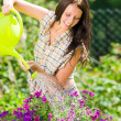Gardening smiling woman watering can violet flower — Stock Photo