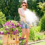 Summer garden smiling woman watering hose flower — Stock Photo #6441190