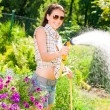 Summer garden smiling woman watering hose garden flower — Stock Photo