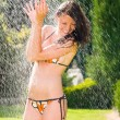 Summer garden smiling woman swimsuit splash water — Stock Photo