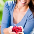 Fresh raspberries hold hand cheerful smiling woman — Stock Photo #6441276