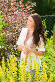 Garden beautiful young woman sunny yellow flowers — Stock Photo