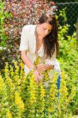Vacker kvinna solig trädgård care gula blommor — Stockfoto