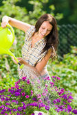 Gardening smiling woman watering can violet flower — ストック写真